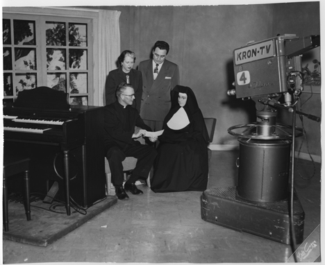 Sisters of the Presentation of the Blessed Virgin Mary Mother Olivia Hargadon work on a San Francisco local television studio set with Father Frank Norris, early 1950s.